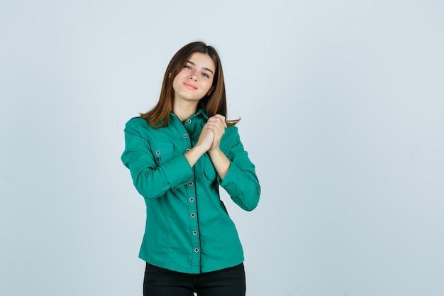 Jovem, segurando as mãos sobre o peito na blusa verde, calça preta e parecendo feliz, vista frontal.