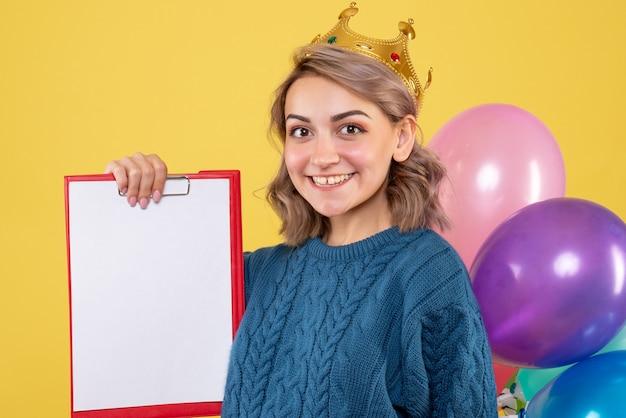 Jovem segurando balões coloridos e uma nota amarela