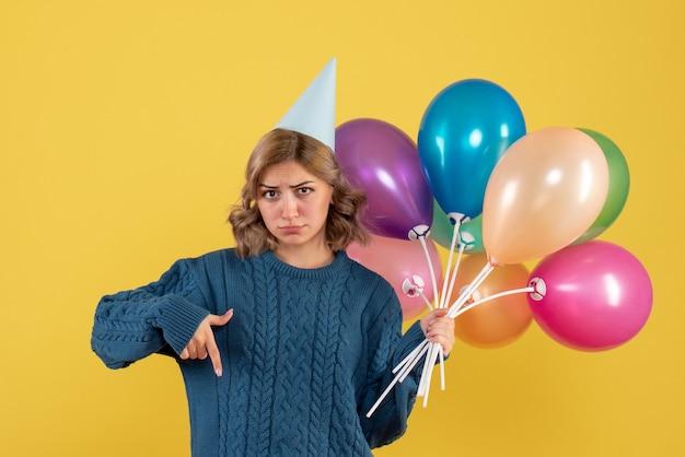 Jovem segurando balões coloridos em amarelo