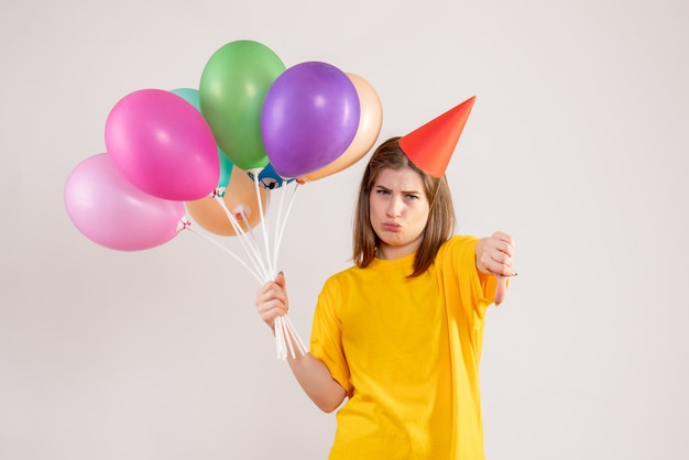 Jovem segurando balões coloridos em branco