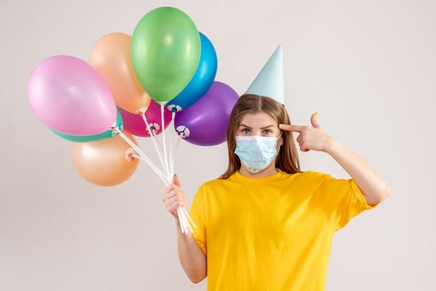 Jovem segurando balões coloridos em máscara estéril em branco Foto gratuita