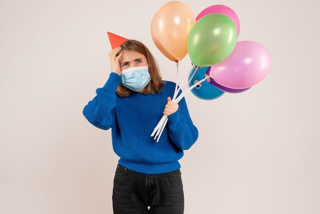 Jovem segurando balões coloridos em uma máscara em branco