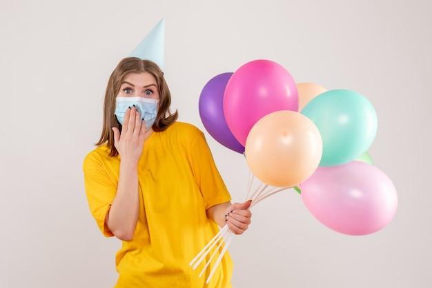 Jovem segurando balões coloridos em uma máscara em branco Foto gratuita