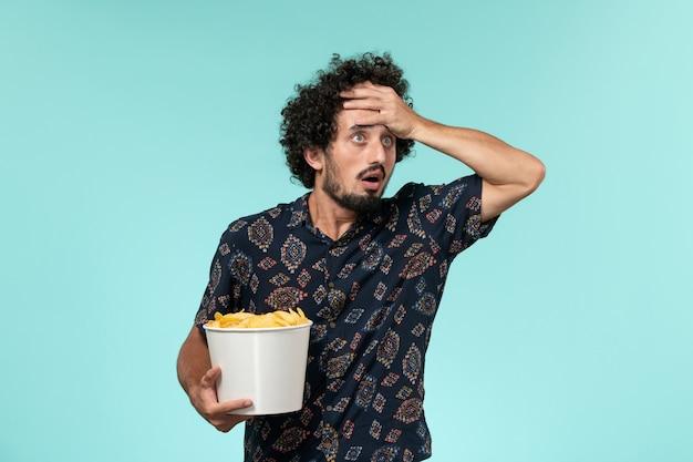Jovem segurando batatas fritas em um cinema de parede azul claro
