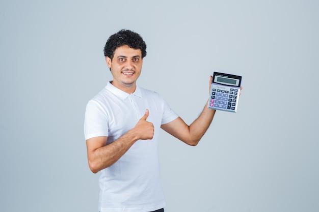 Jovem segurando calculadora, aparecendo o polegar em uma camiseta branca e olhando alegre, vista frontal.