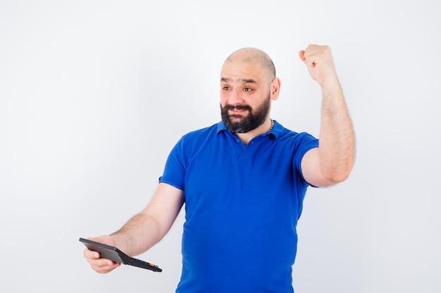 Jovem segurando calculadora enquanto mostra o gesto de sucesso na camisa azul e olhando feliz, vista frontal.