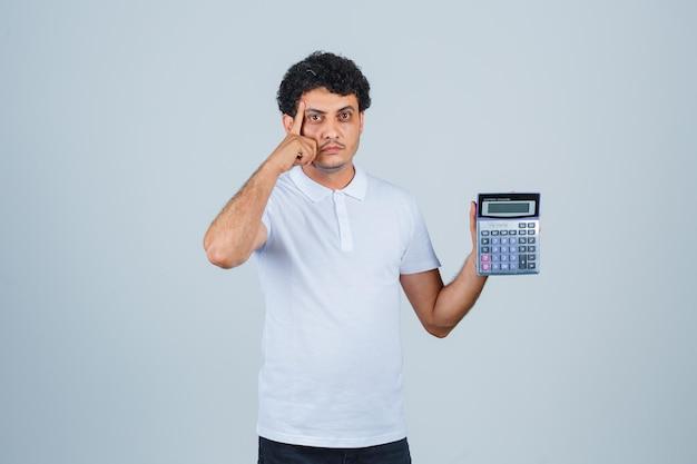 Jovem segurando calculadora enquanto pensa em uma camiseta branca e parece sensata, vista frontal.