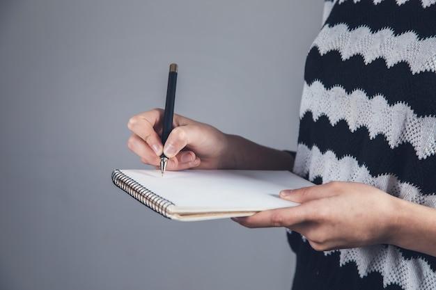 Jovem segurando caneta e caderno