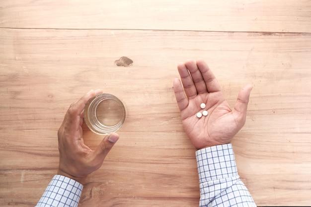 Jovem segurando comprimidos e um copo de água com espaço de cópia