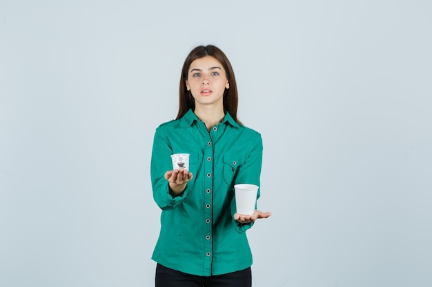 Jovem, segurando copos plásticos de café em uma camisa e olhando confiante, vista frontal.