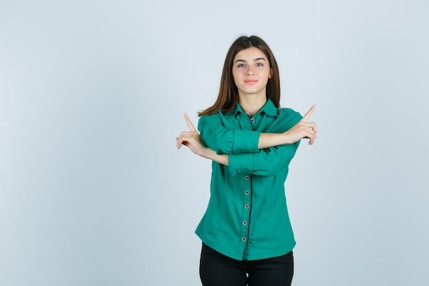 Jovem, segurando dois braços cruzados, apontando para direções opostas com os dedos indicadores em uma blusa verde, calça preta e parecendo feliz. vista frontal.