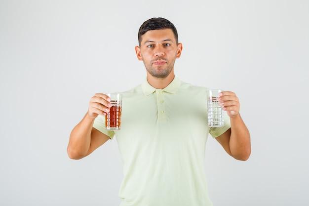 Jovem segurando dois copos de bebida em vista frontal da t-shirt.