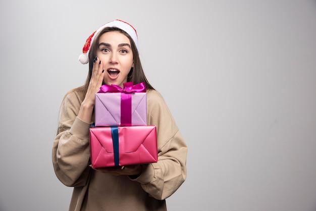 Jovem segurando dois presentes de natal