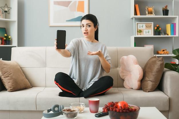 Jovem segurando e apontando com a mão para o telefone, sentada no sofá atrás da mesa de centro na sala de estar