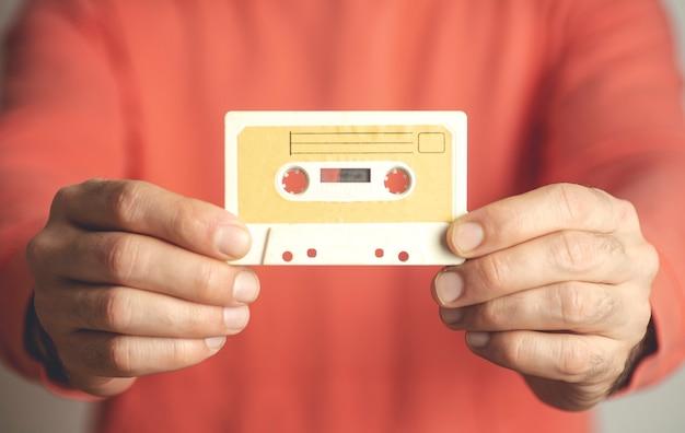 Jovem segurando fita cassete velha vintage com música.