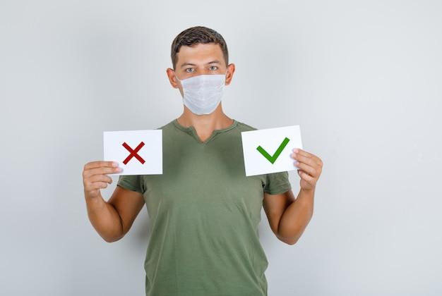 Jovem segurando folhas de papel com opções de camiseta verde exército, máscara, vista frontal.