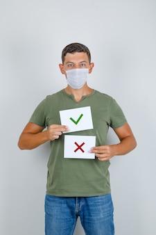 Jovem segurando folhas de papel com opções em t-shirt, jeans, máscara, vista frontal.