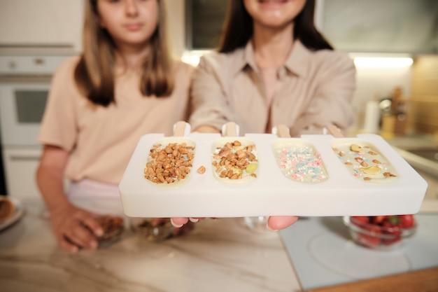 Jovem segurando formulários de silicone cheios de sorvete de esquimó caseiro líquido polvilhado com amendoins com a filha por perto