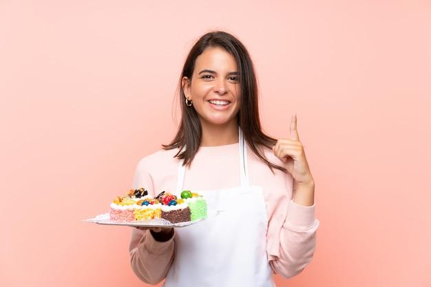 Jovem, segurando muitos mini bolos diferentes sobre parede isolada, apontando para uma ótima idéia