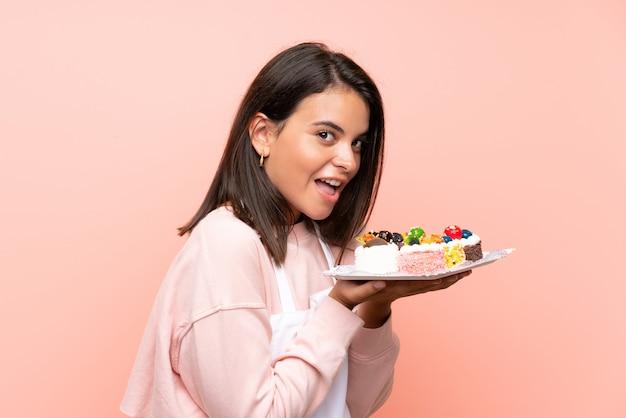 Jovem, segurando muitos mini bolos diferentes sobre parede isolada