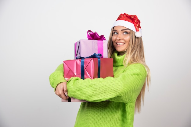 Jovem segurando muitos presentes festivos de natal
