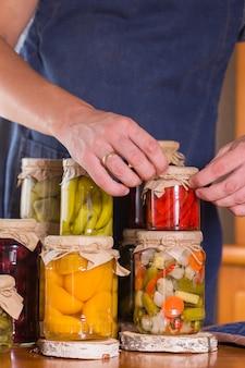 Jovem segurando nas mãos comida em conserva
