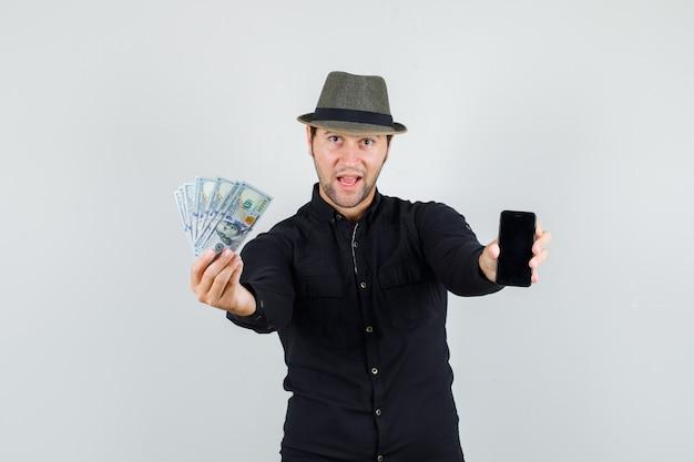 Jovem segurando notas de dólar e smartphone em uma camisa preta