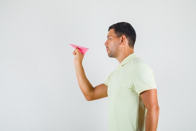 Jovem segurando o avião de papel feito à mão em t-shirt.