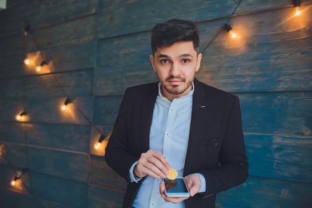 Jovem, segurando o bitcoin na mão