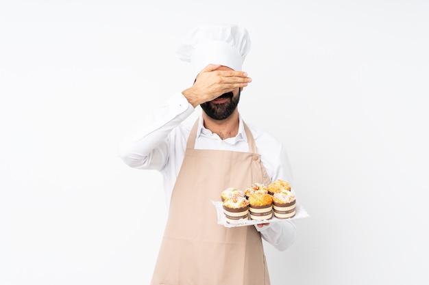 Jovem, segurando o bolo muffin, cobrindo os olhos pelas mãos. não quero ver algo