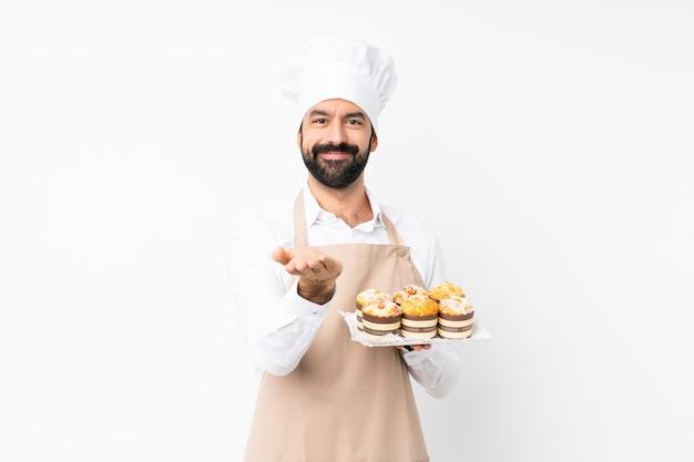 Jovem, segurando o bolo muffin sobre branco isolado segurando copyspace imaginário na palma da mão para inserir um anúncio