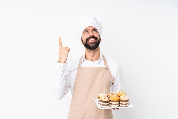 Jovem, segurando o bolo muffin sobre parede branca isolada, apontando para cima e surpreso