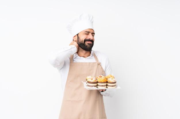 Jovem, segurando o bolo muffin sobre parede branca isolada com dor de garganta