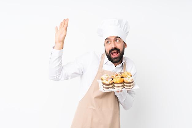 Jovem, segurando o bolo muffin sobre parede branca isolada, nervoso e assustado