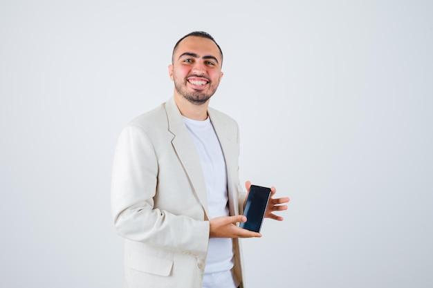 Jovem, segurando o celular em camiseta branca, jaqueta e parecendo feliz, vista frontal.