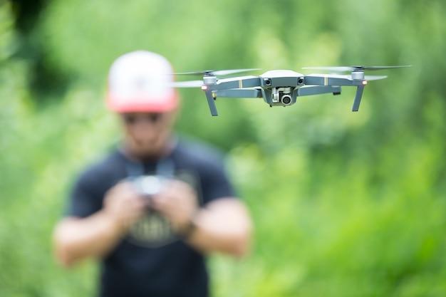Jovem, segurando o controle remoto e voando com o drone no parque.
