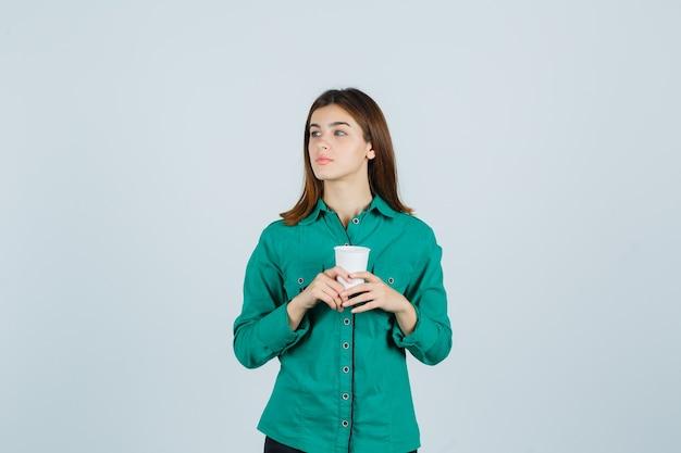 Jovem, segurando o copo plástico de café em uma camisa e olhando pensativa. vista frontal.