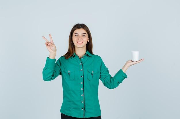 Jovem, segurando o copo plástico de café enquanto mostra o sinal da vitória na camisa e olhando alegre. vista frontal.