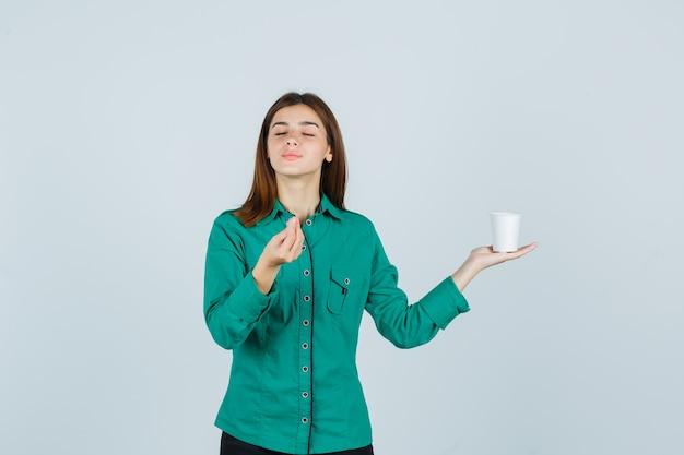 Jovem, segurando o copo plástico de café enquanto mostra um gesto delicioso na camisa e parece satisfeito, vista frontal.