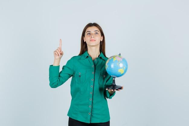 Jovem, segurando o globo terrestre, apontando para cima na camisa e parecendo satisfeito. vista frontal.