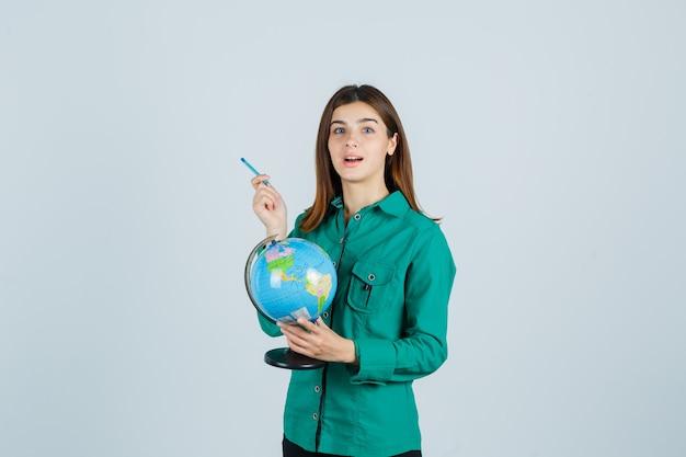 Jovem, segurando o globo terrestre, apontando para o lado com uma caneta na camisa e olhando animada, vista frontal.