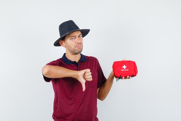 Jovem, segurando o kit de primeiros socorros com o polegar para baixo em t-shirt, chapéu e parecendo decepcionado, vista frontal.