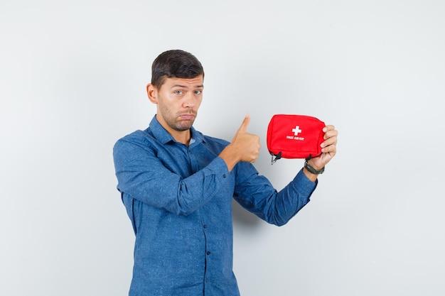 Jovem, segurando o kit de primeiros socorros com o polegar para cima na vista frontal de camisa azul.