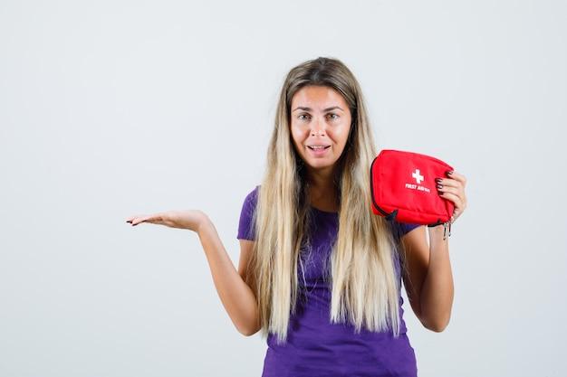 Jovem, segurando o kit de primeiros socorros, espalhando a palma da mão para o lado em uma camiseta violeta, vista frontal.