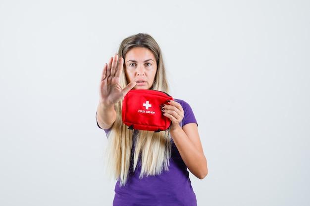 Jovem, segurando o kit de primeiros socorros, mostrando o gesto de parada na camiseta violeta, vista frontal.