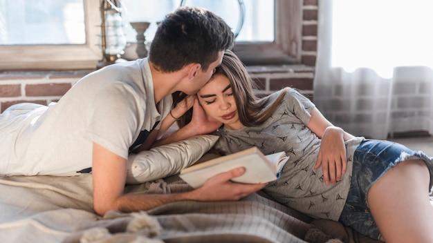 Jovem, segurando o livro na mão, amando a namorada em casa