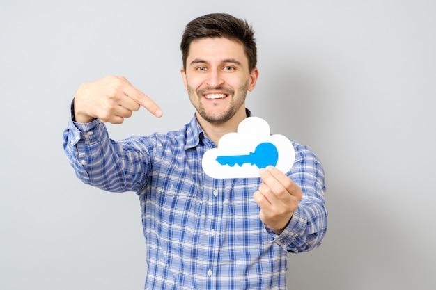 Jovem, segurando o modelo de nuvem com chave azul