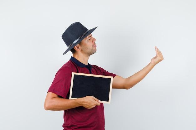 Jovem, segurando o quadro-negro e convidando para entrar em t-shirt, chapéu, vista frontal.