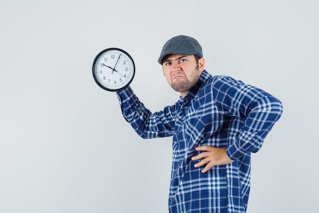 Jovem segurando o relógio de parede enquanto carranca na camisa, boné.