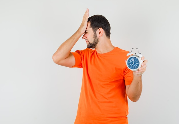 Jovem segurando o relógio despertador com a mão na testa em t-shirt laranja e parecendo esquecido. vista frontal.